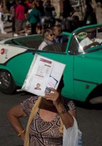 Een Cubaanse vrouw beschermt zich met haar papieren tegen de zon bij de Amerikaanse vertegenwoordiging in Havana