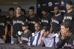 David P. Samson, president van de Miami Marlins bedekt zijn gezicht tijdens de persconferentie, links van hem de trainer