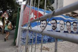 A woman walks near a mural, depicting five Cuban agents held in prison in the U.S. for over ten years, in Havana